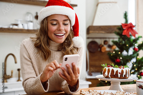 Obraz Happy woman in santa claus hat smiling while using mobile phone - fototapety do salonu