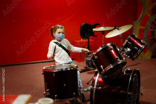 Foto child in a mask plays drums on a red background, a child plays a drum kit, the c