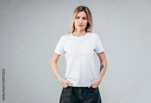 Stylish blonde girl wearing white t-shirt posing in studio Fotobehang