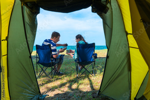 married couple drinking tea while sitting in chairs near the camping by the sea Fotobehang