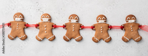 Fototapeta Stay home quarantine from Covid-19. Christmas gingerbread men with a masks obraz