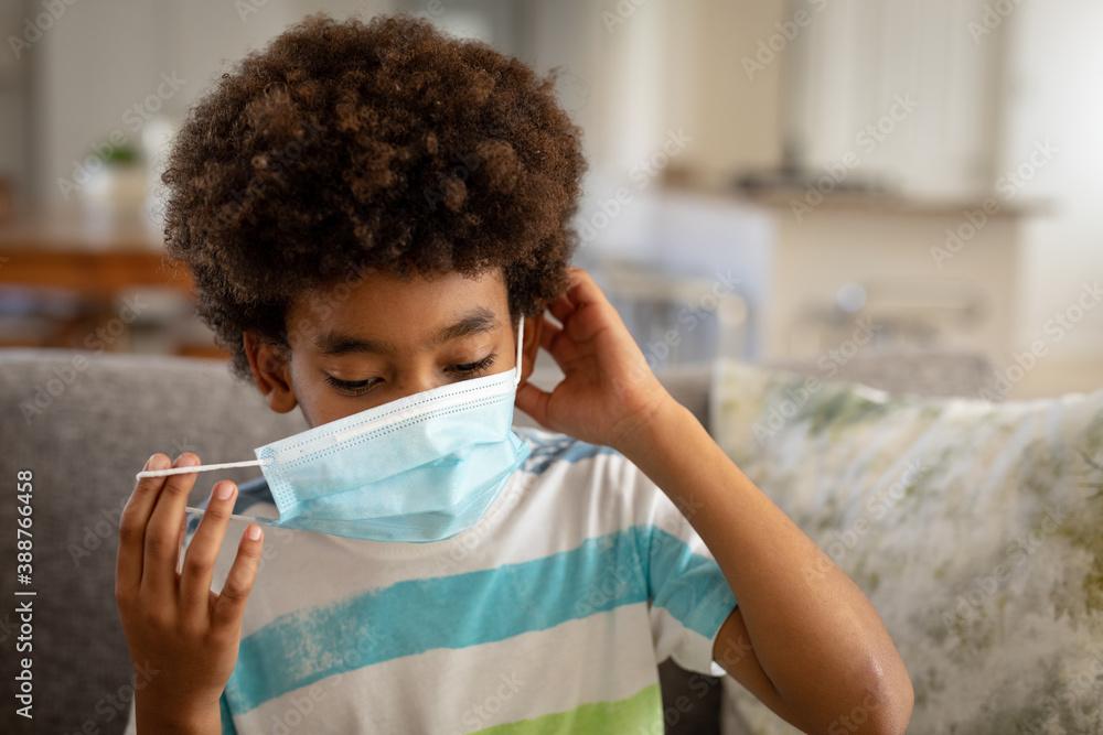 Fototapeta Boy wearing face mask at home