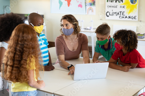 Fototapeta Female teacher wearing face mask using laptop to teach students in class
