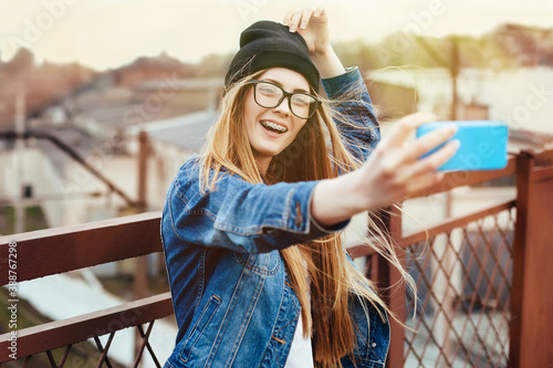 Obraz Young sexy blonde hipster woman posing for selfie and laughing. Wearing jeans jacket, hipster black hat and glasses. Lifestyle portrait bright with sun shine. - fototapety do salonu