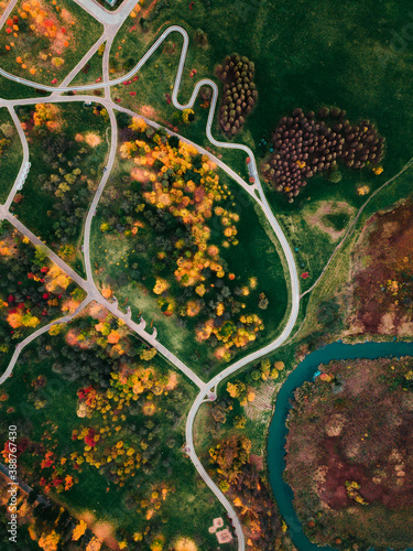 Stunning Aerial shot from above top view on autmn park in Minsk. Yellow leaves. Fall forest trees. Beautiful  bright autmn. Drone shot. Fly above autmn park.