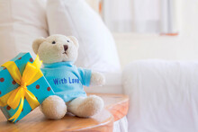Cute Toy Bear With Gift Box On Background Blur White Bed Sheets And Pillows And Leave Space For Adding Your Content.