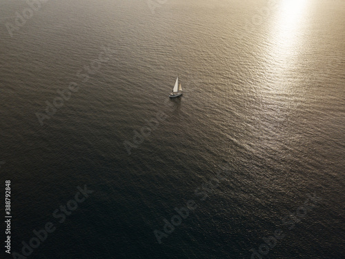 Leinwand Poster Aerial view of a sailboat sailing in the ocean