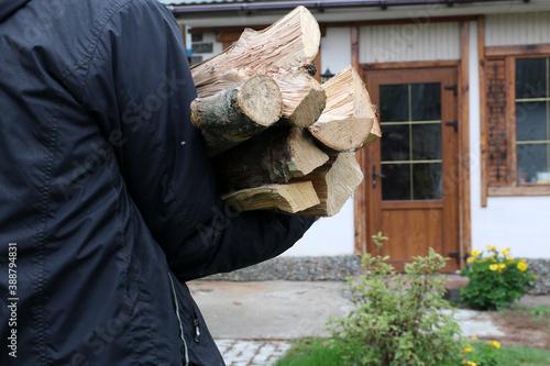 Slika na platnu A man carries firewood for heating the house