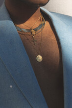 Close Up Of Man Wearing Layered Gold Jewelry