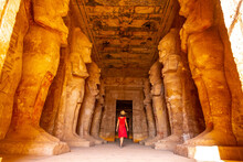A Young Woman In Red Dress Looking At The Pharaohs At The Abu Simbel Temple In Southern Egypt In Nubia Next To Lake Nasser. Temple Of Pharaoh Ramses II, Travel Lifestyle
