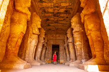 A Young Woman In A Red Dress At The Abu Simbel Temple Next To The Sculptures, In Southern Egypt In Nubia Next To Lake Nasser. Temple Of Pharaoh Ramses II, Travel Lifestyle