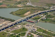 Aerial View Of The Welland Canal In St Catharines Ontario, Ship Passing Under Neath The Garden City Highway Bridge With The Homer Drawbridge Open