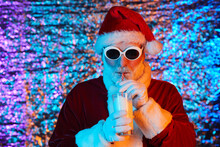Santa Claus In Sunglasses Holding Glass And Drinking Milk From Drinking Straw Against The Shiny Background