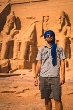 Portrait Of A Young Tourist With A Blue Turban Visiting The Abu Simbel Temple In Southern Egypt In Nubia Next To Lake Nasser. Temple Of Pharaoh Ramses II, Travel Lifestyle