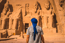 A Young Tourist In A Blue Turban Looking At The Abu Simbel Temple In Southern Egypt In Nubia Next To Lake Nasser. Temple Of Pharaoh Ramses II, Travel Lifestyle