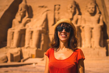 A Young Tourist In A Red Dress Smiling At The Abu Simbel Temple In Southern Egypt In Nubia Next To Lake Nasser. Temple Of Pharaoh Ramses II