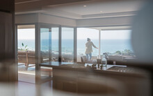 Woman Looking At Sunny Ocean View On Luxury Home Showcase Balcony