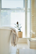 Towel Hanging Over Soaking Tub In Luxury Home Showcase Bathroom