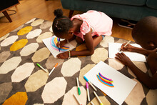 Girl Drawing Multicolor Rainbow With Markers On Living Room Rug