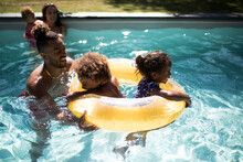 Family Playing With Inflatable Ring In Sunny Summer Swimming Pool