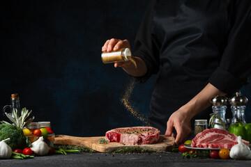 Professional chef in black uniform pours mustard on raw steak on wooden chopped board. Backstage of preparing grilled pork meat at restaurant kitchen on dark blue background. Frozen motion.