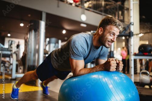 Obraz Portrait of fit handsome man workout on a fitness machine at gym - fototapety do salonu