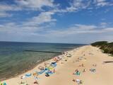 Fototapeta Fototapety z morzem do Twojej sypialni - Widok na morze i plażę gdzie widać turystów. Kolorowe koce oraz parawany.