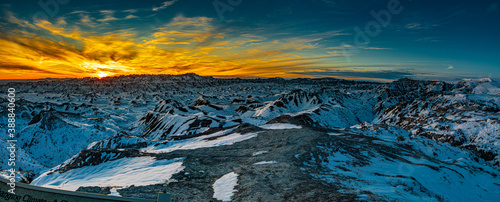 Fototapeta Beautiful and colorful panorama blue hour sunset over snow covered mountains and ridges of Badlands National Park