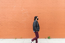 Man In Face Mask Walking Past Brick Wall
