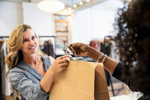 Female Shop Owner Giving Shopping Bag To Customer In Boutique