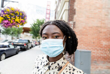 Portrait Beautiful Young Woman In Face Mask On City Sidewalk