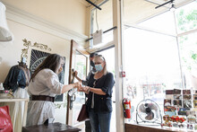 Shop Owner In Face Mask Greeti...