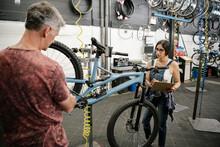 Bike Shop Mechanics Fixing Bic...