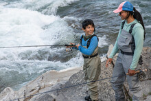 Mother And Son On Rocks Fishing In River