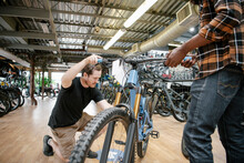 Male Bike Shop Owner Helping C...