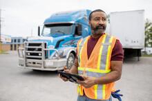Warehouse Worker Using Digital Tablet Near Truck