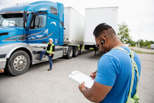 Trucker Looking At Paperwork For Container Semi Truck