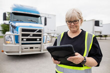 Warehouse Owner Using Tablet Near Container Semi Truck