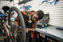 Male Bike Shop Owner Fixing Bicycle Wheel In Workshop