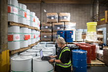 Warehouse Owner Doing An Inventory Of Drums In Distribution Depot