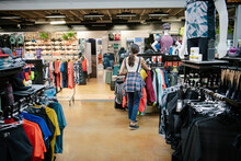 Female Bike Shop Owner Arranging Clothing Merchandise