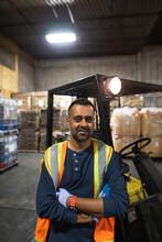 Portrait Of Worker Beside Forklift In Distribution Warehouse