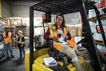 Worker Texting On Phone In Forklift In Distribution Warehouse