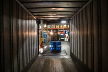 Woman Checking Drums Beside Container In Loading Bay