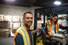 Portrait Of Distribution Warehouse Workers By Forklift