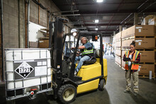 Worker Checking Forklift Driver Loading Container
