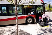 Man In Wheelchair Boarding Public Bus Ramp