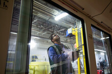 Male Transit Worker Inspecting Subway In Maintenance Facility