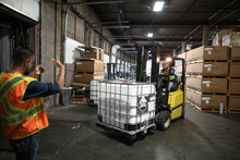 Worker Directing Forklift Driv...