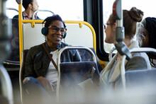 Happy Female Passengers Talking On Public Bus